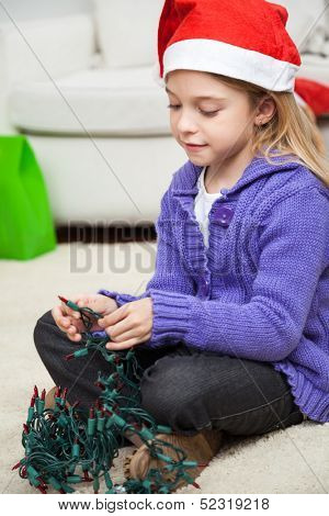 Girl in Santa hat with fairy lights sitting on floor at home during Christmas