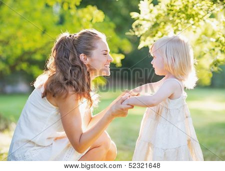 Happy Mother Playing With Baby Outdoors