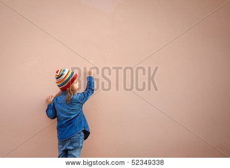 Little girl in jeans writing on the wall