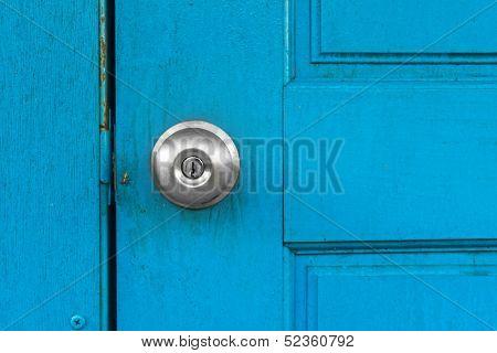 Blue old door with silver door knob.