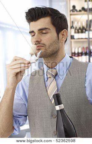 Wine-taster smelling cork eyes closed after opening bottle of wine.