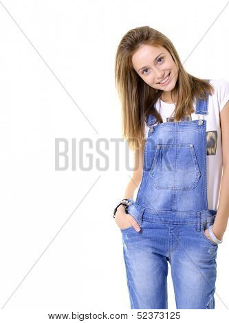 Beautiful cheerful teen girl in blue denim catsuit looking at camera and happy smiling. Isolated on white background