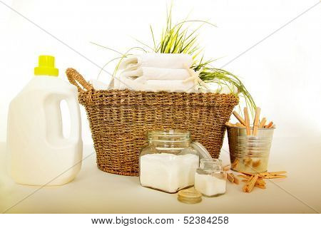 Fresh white towels with liquid soap, powder and clothespins for the laundry day