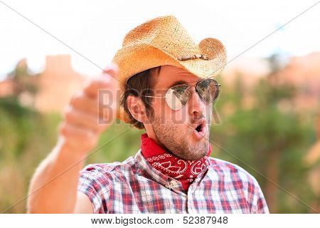 Cowboy man with sunglasses and cowboy hat pointing at camera saying WE WANT YOU. Male model in american rural western countryside landscape nature on ranch or farm, Utah, USA.