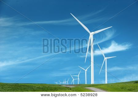 Wind Turbines In An Open Field On Cloudy Day