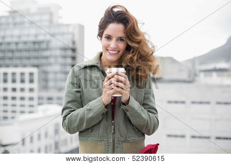 Smiling gorgeous brunette in winter fashion holding disposable cup on urban background