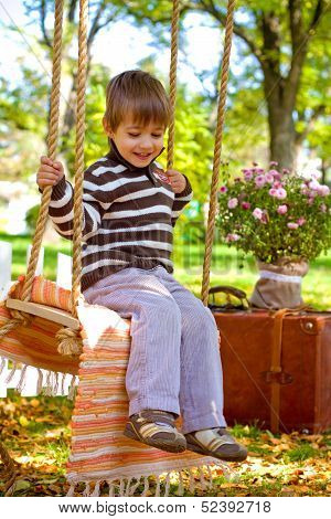 Little Boy Sitting On A Swing In The Autumn Park