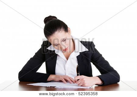 Beautiful attractive corporate lawyer business woman sitting at desk and writing blank paper page, isolated on white background.