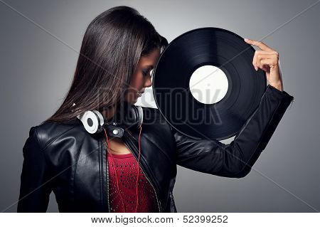 Woman dj portrait with vinyl record and headphones