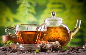 Cup of tea and teapot with blooming tea on blur green background poster