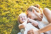 Happy mother and baby laying on meadow poster
