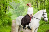 Laughing girl riding horse in the forest poster