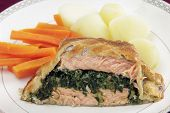 Salmon fillet stuffed with a spinach mixture and encased in puff pastry, served with boiled new potatoes and julienned carrots. poster