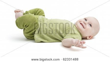 Happy Toddler Lying On His Back In Green Clothing