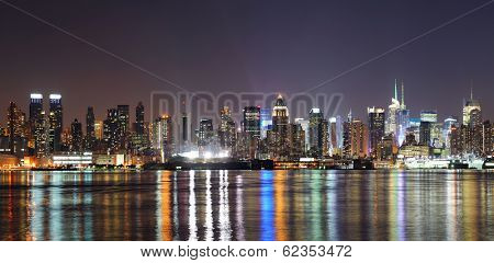 New York City Manhattan midtown skyline at night with lights reflection over Hudson River viewed from New Jersey Weehawken waterfront.