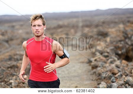 Man running - trail runner cross country training outdoors for marathon or triathlon ironman. Handsome male athlete working out on Hawaii, Big Island, USA. Triathlete listening to music on smart phone