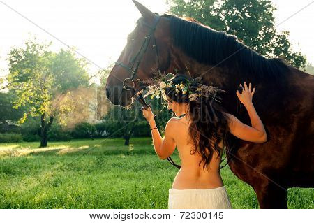 Young pretty nude brunette woman with horse in summer forest poster