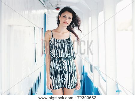 Young sensual brunette woman in dress on the ship deck