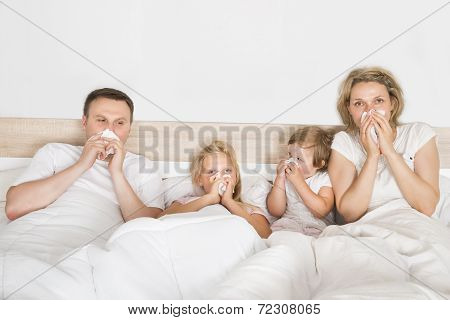 Sick Family Lying In Bed