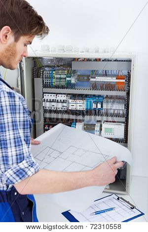 Technician Analyzing Blueprint In Front Of Fusebox