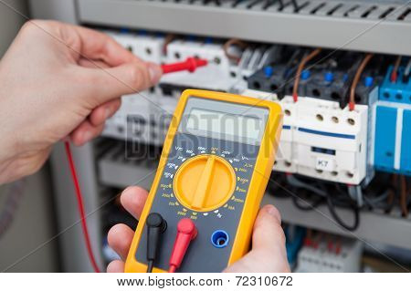 Electrician Examining Fusebox With Resistance Tester