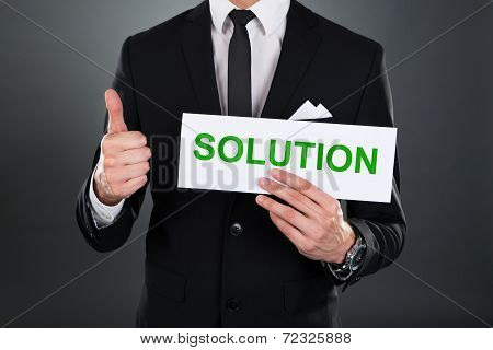 Businessman Gesturing Thumbsup While Holding Solution Sign