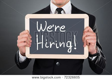 Businessman Holding Slate With We're Hiring Sign