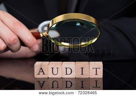 Businessman Examining Audit Blocks Through Magnifying Glass