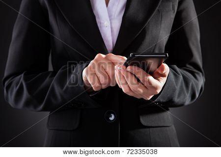 Businessperson Holding Black Cellphone Over Black Background