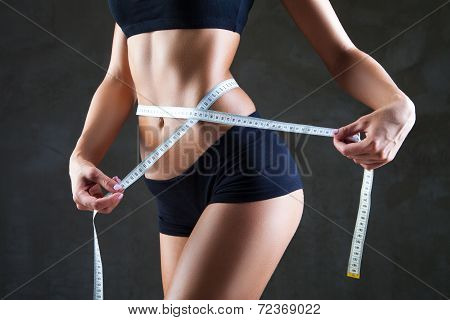 Athletic slim woman measuring her waist by measure tape after a diet over dark gray background poster