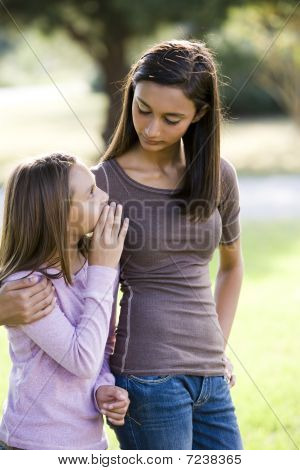 Girl whispering to her older teenage sister