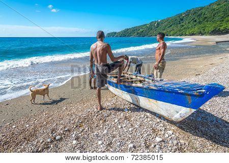 Unidentified local fishermen on Playa San Rafael Barahona Dominican Republic preparing their boat fo