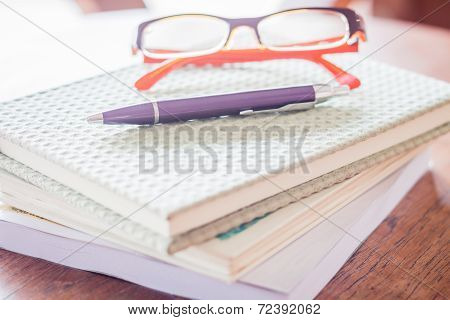 Pen And Eyeglasses On Three Notebooks