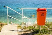 Orange trash bin near the sea beach. Littering the beach and the sea. poster
