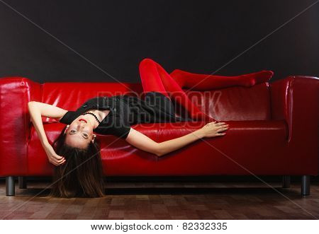 Fashionable woman with long legs in red vivid color pantyhose relaxing on couch indoor on black poster