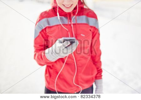 Girl in activewear holding mobile phone during outdoor training