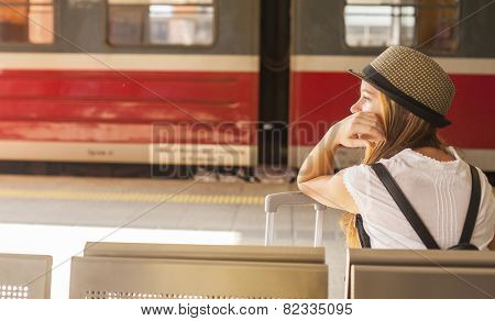 Young cute girl waiting for the train at the railway station. Travel concept.