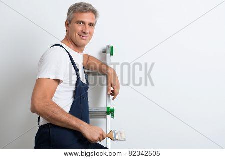 Happy Mature Painter Standing On Stepladder Holding Brush