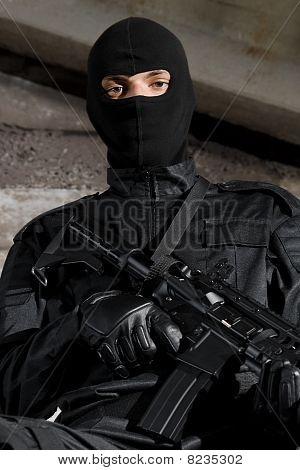 Soldat i svart Uniform med en pistol