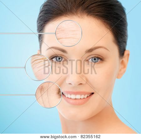 people, skin care and beauty concept - face of beautiful happy young woman over blue background