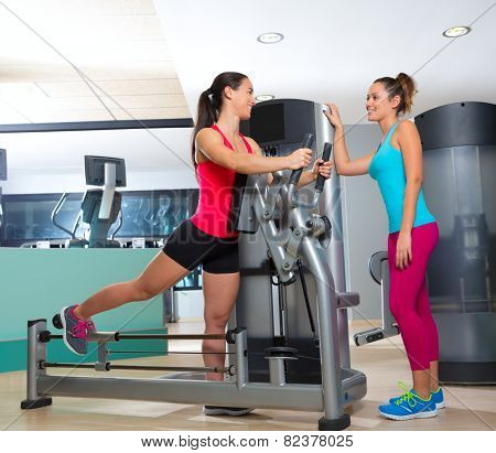 Gym glute exercise machine women workout smiling with personal trainer