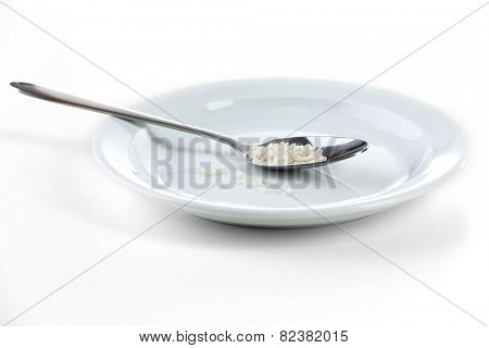 Remnants of rice in spoon on plate isolated on white