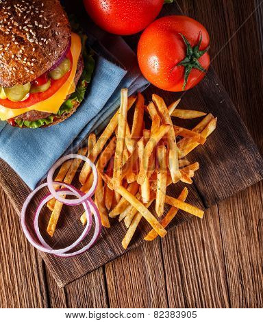 Homemade burger and french fries in dramatic light. Vintage burger or hamburger on old wooden background. Homemade fast food concept. Mouthwatering french fries and burger. Delicious burger with french fries. Burger and fries on wooden table vintage style