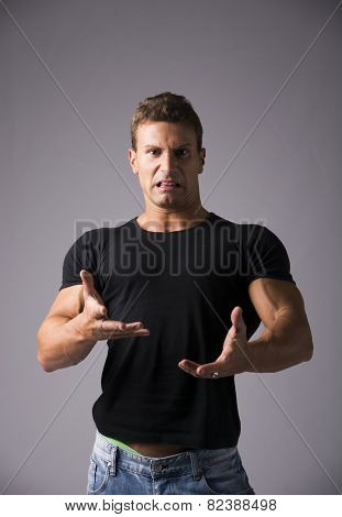 Disgusted young man with funny expression on his face looking at camera. Studio shot on grey background poster
