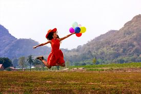 Happy Jumping Woman With Bunch Of Colorful Air Balloons At The Meadow