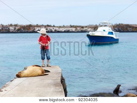 Female sea lion relaxing close to a boy at coast of South Plaza island Galapagos