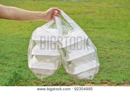 hands holding a clear plastic bags containing three foam containers