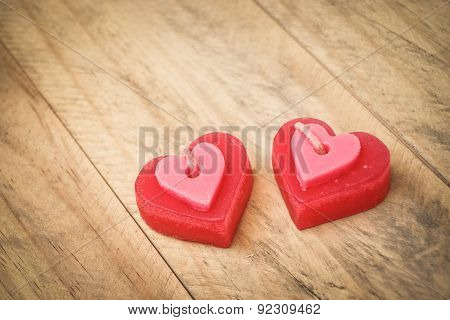 two red scented candles with shapes of a heart on wood plank floor. Valentine's Day