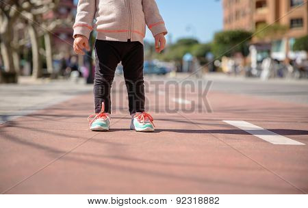 Little girl with sneakers and leggins standing over a city runway