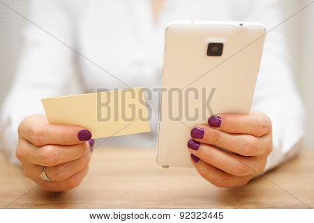 Woman Reading Telephone Number From Business Card And Calling Customer On Smart Mobile Phone